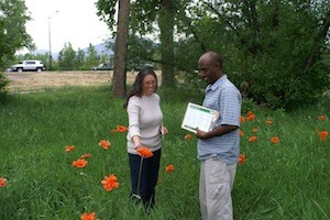 A man and woman outdoors in a place with grass and orange flowers with trees in the background.