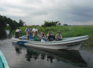 Birders in a boat with binoculars and cameras.
