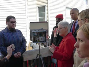 EPA Administrator Gina McCarthy in a red suit demonstrating an air sensor to community members in Newark, New Jersey.