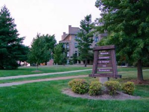 Sign in large lawn with institutional building in back.
