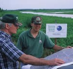 Two men in a wetland looking at a map together.