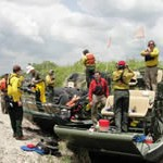 A group of U.S. Fish and Wildlife Service firefighters and the production crew of a Discovery Channel show preparing to ride two airboats.