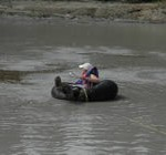 Woman floating in an inner tube on the surface of Upper Klawasi mud volcano in order to collect a sample.