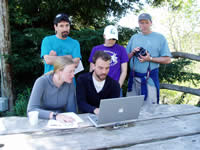 Three people standing and two sitting at a picnic table reviewing data on a laptop.